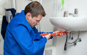 Emergency plumber fixes a leaking sink drain